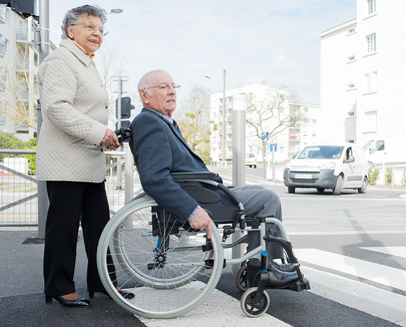 woman pushing man in wheel chair